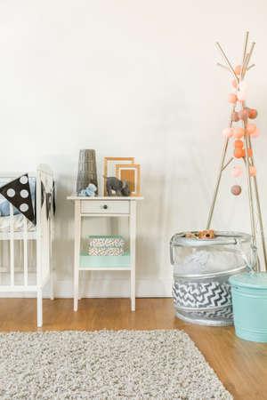 nursery: Imagen de la cuna y una pequeña mesa con accesorios infantiles Foto de archivo