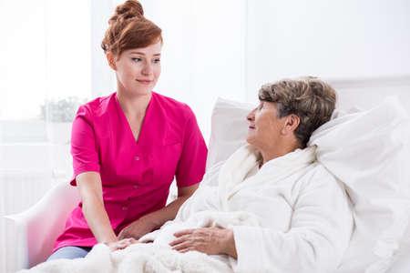 geriatric nurse: Image of young nurse and geriatric ward female patient