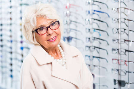 trying on: Elder woman trying on glasses in optical shop