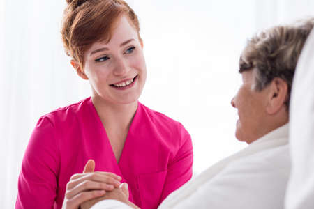 geriatric care: Portrait of positive smiling carer working in rest home Stock Photo