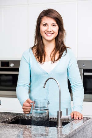 filtration: Girl using water filtration faucet in the kitchen Stock Photo