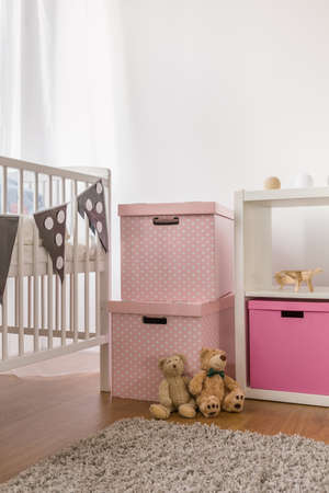 white interior: Photo of white cot and pink boxes in child bedroom