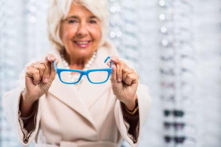 glasses model: Senior woman holding glasses with blue frame