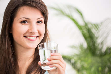 Fit girl drinking glass of mineral water