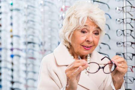 수석 여자 안경점에서 안경에 노력 스톡 콘텐츠