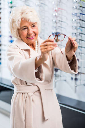 shortsightedness: Female retiree choosing new spectacles to reading