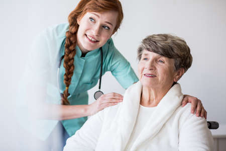 Picture of young doctor and elderly patient of geriatric ward