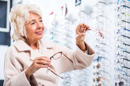 shortsightedness: Female customer choosing eyeglasses in optician store Stock Photo