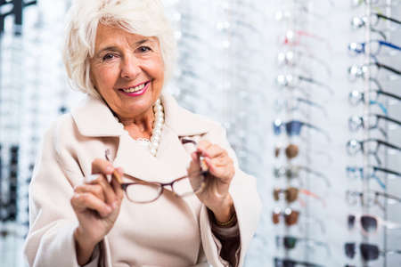 shortsightedness: Female retiree choosing eyeglasses in optician store