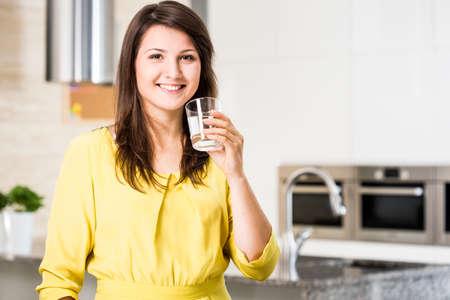 llave de agua: Mujer bonita que bebe mujer filtrada en casa