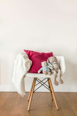 baby chair: Image of white baby blanket and toy on chair Stock Photo