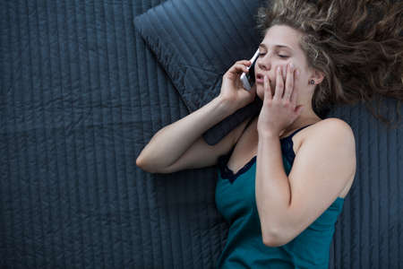sick person: Picture of sleepy female in nightgown talking on phone