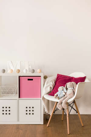 bedroom: Photo of white cabinet and chair in child bedroom Stock Photo