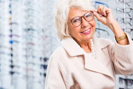 mulher: A mulher idosa escolher óculos de leitura em loja de óptica