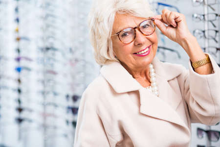 Elderly woman choosing reading glasses in optical shop