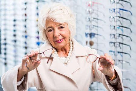 shortsightedness: Senior woman having hard decision - which glasses choose Stock Photo