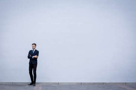 exterior wall: Young handsome businessman in suit standing outdoors