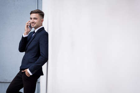 Handsome businessman talking on the phone outdoors Stock Photo