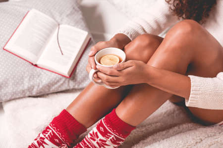 reading book: Girl in wooden socks enjoying a winter time