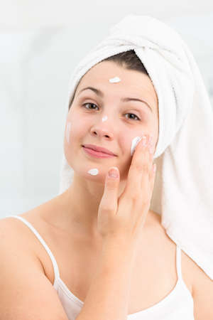 female in douche: Picture of female applying moisturizing face cream