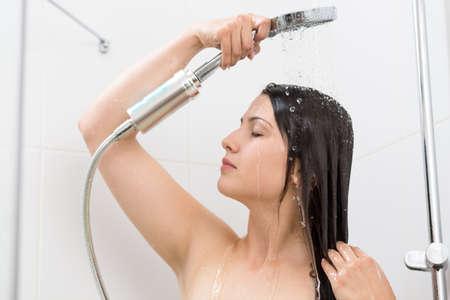 female in douche: Photo of young beautiful woman taking relaxing shower