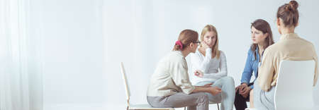 Panorama of women sitting in circle during session with psychologist