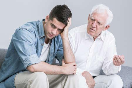 Troubled jonge man te praten met een oudere vader