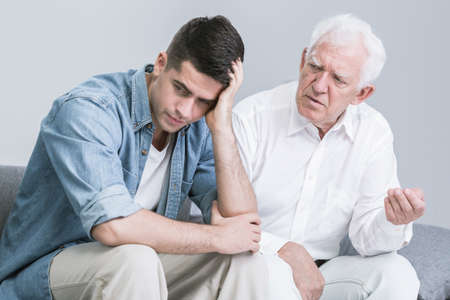 grandfather and grandson: Troubled young man talking with elder father Stock Photo
