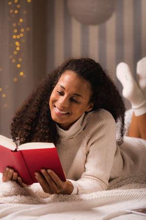 lying in bed: Teen girl reading romance novel in bed