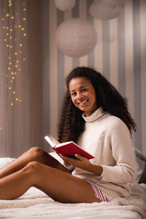 bed time: African American woman with book in the bed