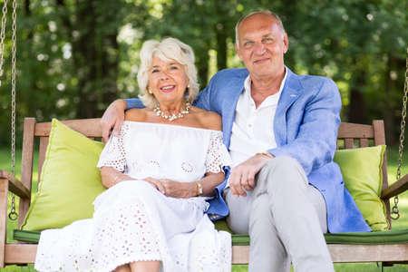 retirement happy man: Photo of elegant senior wife and husband relaxing in garden