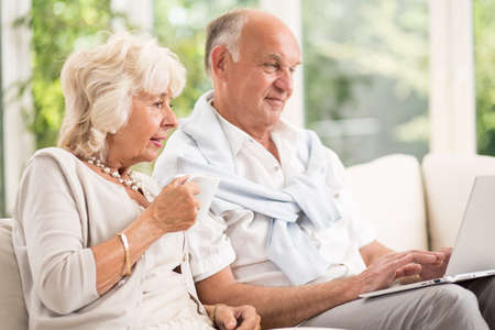 Image of modern elderly married couple using laptop