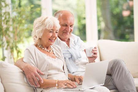 Photo of happy senior pair with computer skills