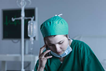 Picture of female doctor wearing sterile uniform talking on phone