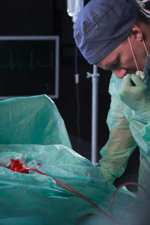 surgical department: Image of focused male surgeon in sterile scrubs during operation