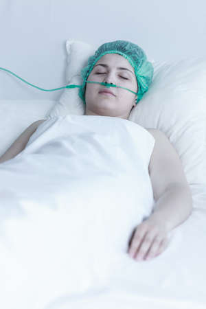 surgical department: Picture of young sleeping female patient after surgical intervention Stock Photo