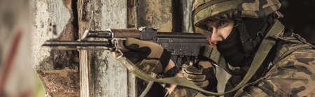 sniper training: Close-up of young soldier aiming by rifle in enemy