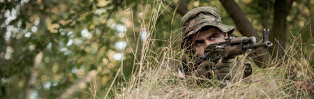 concentrated: Young concentrated warrior in uniform hide in bushes Stock Photo