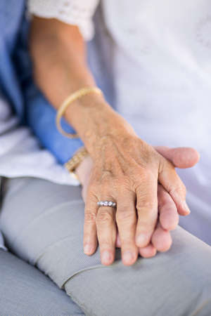 Close up of wife holding hand of her beloved husband