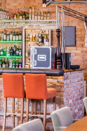 industrial design: Brick walls and orange stools in industrial bar Editorial