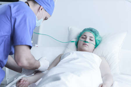 surgical department: Picture of surgeon injecting ill woman lying in bed