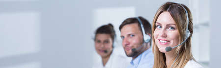 handsfree phone: Young smiling people are working at telemarketing