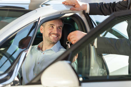 car loans: Picture of showroom client sitting in his new car