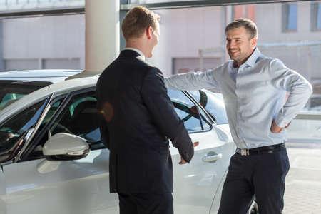 Beeld van de glimlachende autoshowroom klant praten met de verkoper