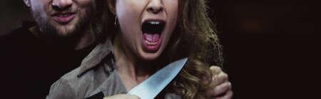 cuchillo: Panorama de bandido psicópata con un cuchillo atacando aterrorizada mujer Foto de archivo
