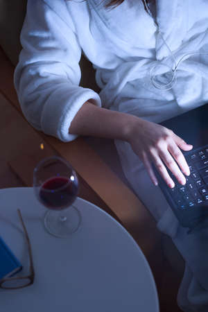 surfing the net: Young woman drinking wine and surfing the net Stock Photo
