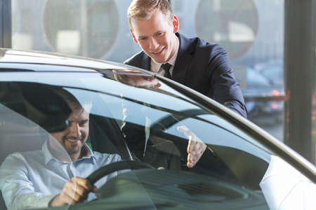 test drive: Image of car dealer with client preparing to test drive