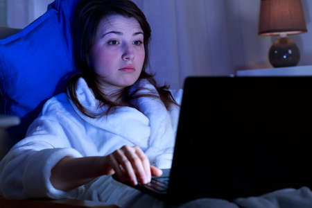 addiction: Girl addicted to computer surfing on the internet