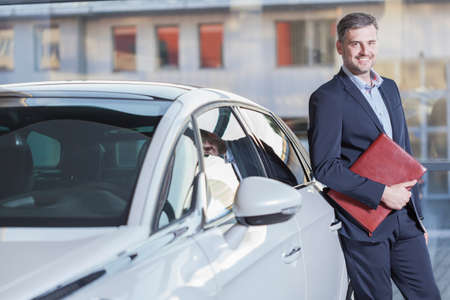 automobile dealership: Image of smiling businessman with his new luxurious automobile Stock Photo