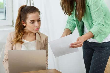 empleados trabajando: Photo of female manager explaining something to young worker